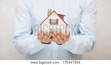 Small toy house in hands