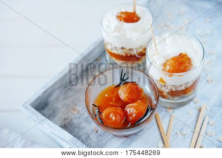 Oats layered with spicy and sweet apricot jam and cream served for breakfast. Healthy food concept.