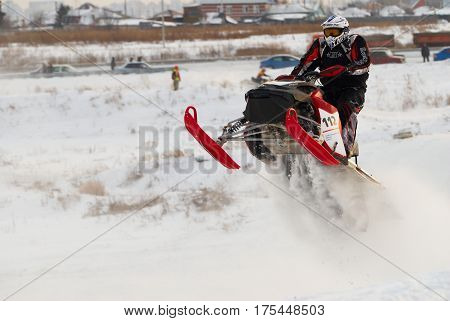 Tyumen Russia - December 26. 2009: Sport snowmobile racing on championship of Ural region. Sportsman on snowmobile on track