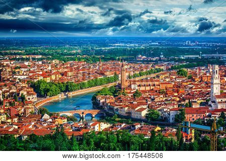 Panorama Italy town Verona and river Adige with dramatic sky urban landscape green tree bridge high tower.