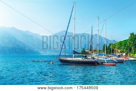 Sailing boats yachts on Garda lake, Veneto region, Italy. Landscape of marine regatta with floating boats in the harbor with high Alpine mountains background
