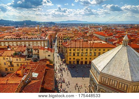 Panoramic view Baptistery of San Giovannito in Florence and tile roofs old town houses. Green hills blue sky with clouds summer landscape on background. Firenze, Italy.