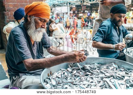Amritsar, India - August 15, 2016: Sikh volunteers in Golden Temple free canteen. This is the biggest free eatery in the world in Golden Temple, Amritsar, India