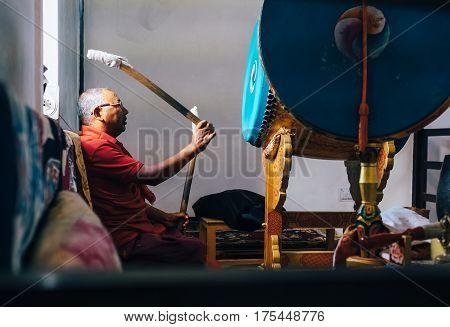 Shanti Stupa  Leh district, India - August 23, 2016: Tibetan monk beats praying Drum during ritual orison