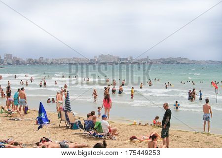 Плавающие и загорающие люди на пляже в городе Аликанте, Испания, лето 2014