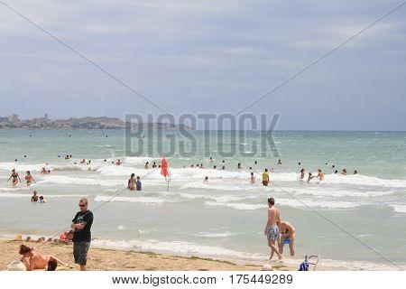 Плавающие в море множество людей в пасмурную погоду в городе Аликанте, Испания, лето 2014
