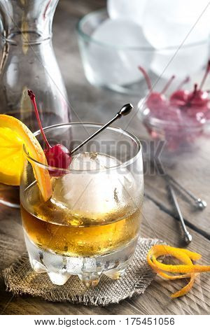 Old fashioned cocktail with maraschino cherries on the board