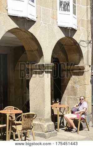 SANTIAGO DE COMPOSTELA, SPAIN - AUGUST 5, 2016: Woman pilgrim sitting at an outdoor bar in the old town of the city in Santiago de Compostela Galicia Spain