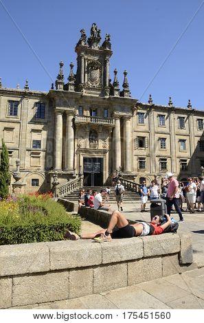 SANTIAGO DE COMPOSTELA, SPAIN - AUGUST 5, 2016: Pilgrim resting next the Monastery of San Martin Pinario Santiago de Compostela Galicia Spain.