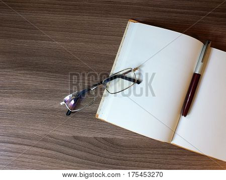 Open notepad with pen and glasses on the wooden table