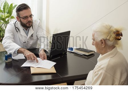 Doctor explains patient record in the documents.A doctor shows a finger writing in the medical history of the patient.The doctor explains and shows the results of a patient