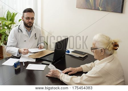 geriatrician doctor with a patient in his office.Old woman at the doctor geriatrician.The doctor geriatrician with a patient. Receives documents from the patient.