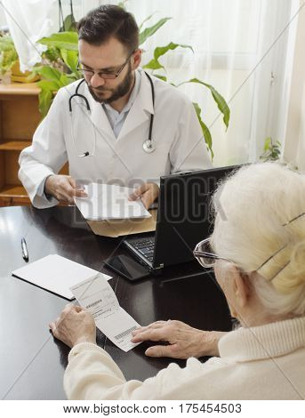 doctor's office. A doctor takes a patient. The patient, an old woman reading a record on the prescription issued by a doctor.