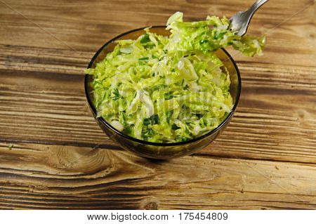 Savoy Cabbage Salad  In Glass Bowl On Wooden Table. Fork With Salad