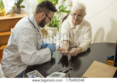 A private doctor's office. Doctor examining an old woman's hand.