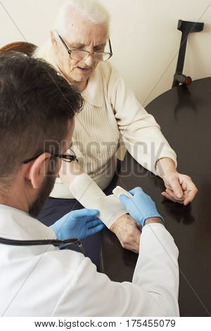 A private doctor's office. Doctor examining an old woman's hand. Old woman at the doctor. The doctor provides the patient's hand. Bandage the hand by a doctor.