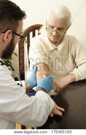 Doctor in the office with a syringe. Administration of intravenous injection by a doctor old woman.
