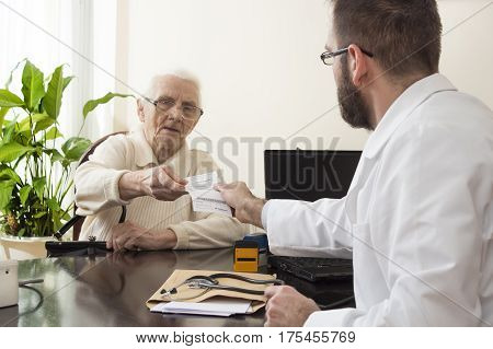 geriatrician doctor with a patient in his office.Old woman at the doctor geriatrician.The doctor gives the patient a prescription.