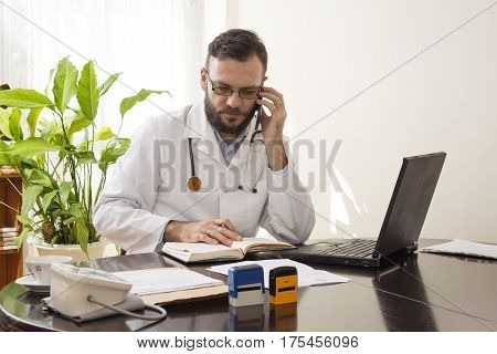 Doctor in the doctor's office talking on the phone and checks for available dates on the calendar.