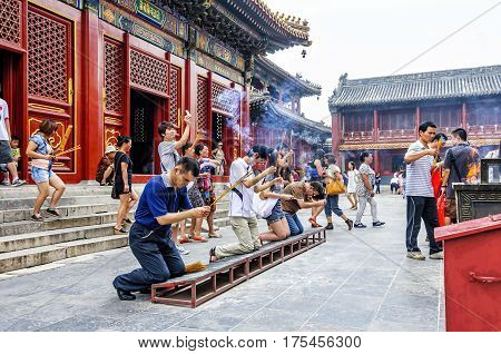 Beijing, China - August 18, 2011: Worshipers at the Yonghe Temple. Also known as the Lama Temple, is a monastery of the Gelug school of Tibetan Buddhism located in Dongcheng District, Beijing, China