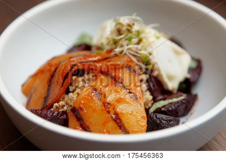 Appetizer of baked beetroot and marinated grilled pear in porcelain plate