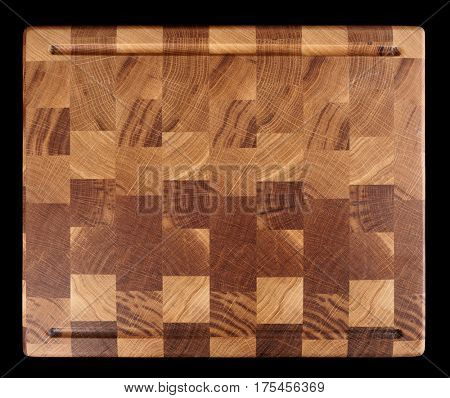 Wooden cutting board isolated on black background shot from above