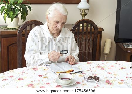The old woman sits at a table with a newspaper. Grandmother reading a newspaper holding a magnifying glass. Grandma reads a newspaper article with a magnifying glass.