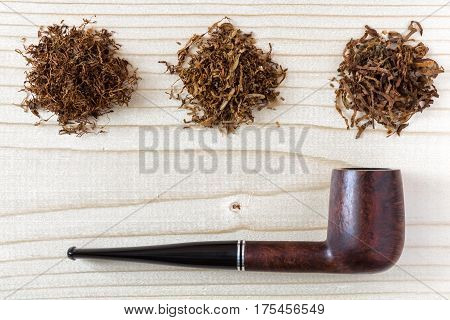 Three different sorts of finer and larger cuts Tobacco and simple straight Pipe on natural wood Background