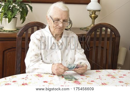 The old woman counting money while sitting at the table.  Pension. Old woman counts the money.  Old woman with a sad face counts money while sitting at the table.