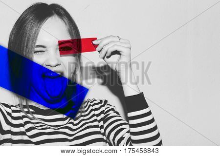 Young attractive emotional girl show tongue in strip dress holding and looking through colorful camera roll plastic film strips like sunglasses. Positive woman having fun