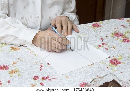 Hands of the old woman who writes handwritten testament on a piece of paper