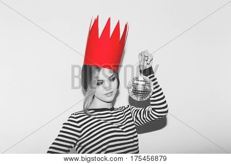 Young sad woman on white background at party, wearing stripped dress and red paper crown, carnival disco ball party. Black and white.