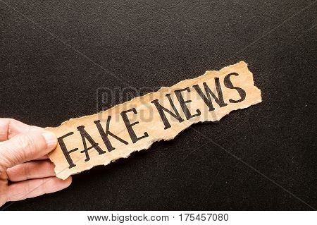 Torn paper with text FAKE NEWS in his hand man against the background of the chalk board
