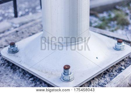 Larger Screws Into The Base Of A Metal Pillar.