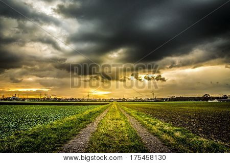 Old field path with houses extreme vanishing point perspective and dramatic sky