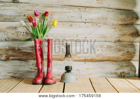 colorful rain boots with spring flowers and oli lamp in wooden background.
