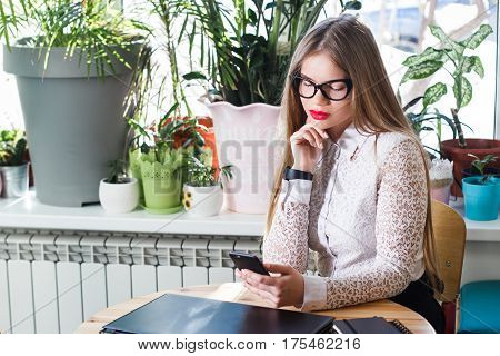 Attorney - young asian woman lawyer looking at mobile smartphone and drinking coffee from disposable paper cup. Young multiethnic female professional in the city in front of courthouse.