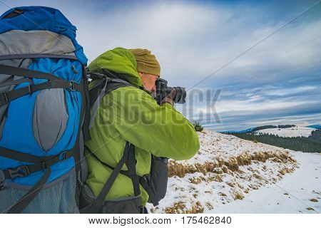 Hiker with a camera and big backpack taking photos of beautiful winter mountain valley with dramatic clouds in a sky. Carpathians Ukraine Europe.