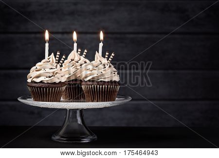 Three chocolate cupcakes with buttercream icing and Birthday candles on a cake stand