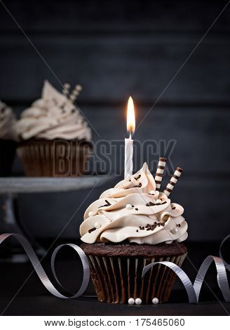 Chocolate Birthday cupcake with buttercream icing over a dark background