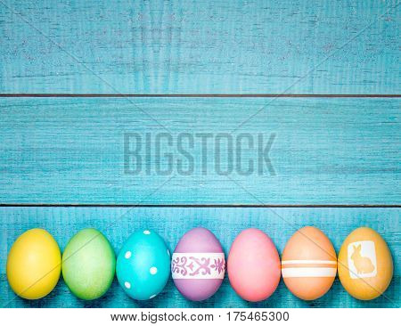 Colorful Easter Eggs arranged in a row on a blue background.