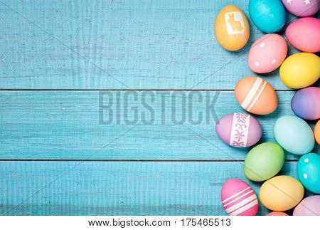 Colorful Easter Eggs arranged to one side on a blue background.