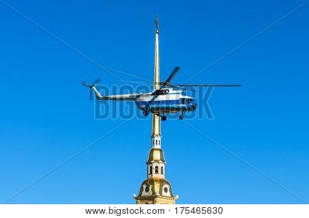 Helicopter in the sky against the spire of the Peter and Paul Fortress in St. Petersburg.