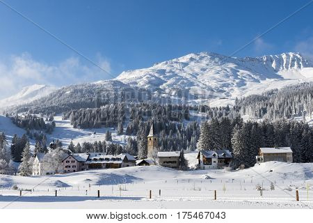 Sunny winterday in the small town of Parpan with church mountains farms and houses in kanton Graubunden in Switzerland.