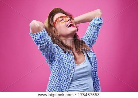Close-up shot of elated girl with closed eyes laughing. Wearing checked shirt, hat and glasses. Relaxed and carefree teenager
