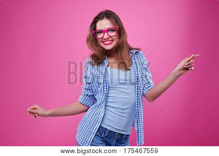 Close-up shot of beguiles girl having fun isolated over pink background. Female in casual outfit dancing and spending time with pleasure