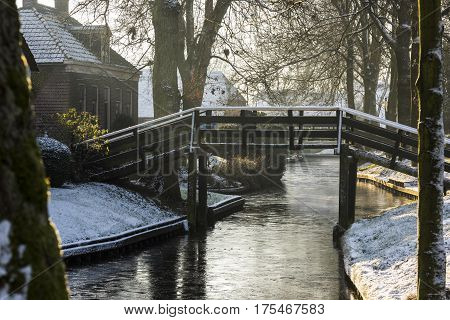 Winterlandscape with canal farmhouse and bridge in the typical dutch village of Giethoorn in the province of Overijssel in the Netherlands.