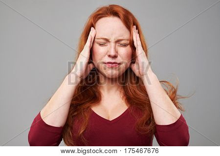 Close-up shot of stressed woman with headache holding her hands on head. Woman isolated over background