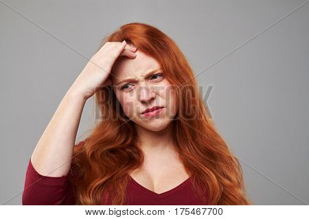 Close-up portrait of young woman having a headache isolated over gray background. Woman feeling bad. The concept of heath care