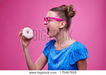 Side view of stylish girl is going to bite a sprinkled doughnut. Woman with double buns wearing dotted blue dress